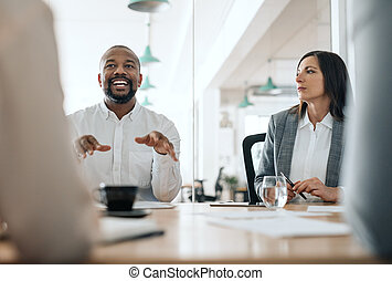 Smiling African American businessman talking with colleagues during a meeting