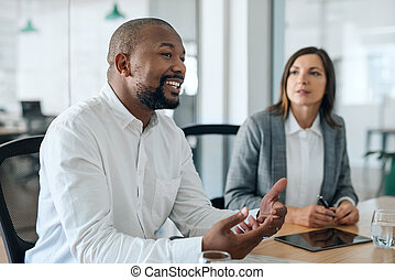 Smiling African American businessman talking with coworkers during a meeting