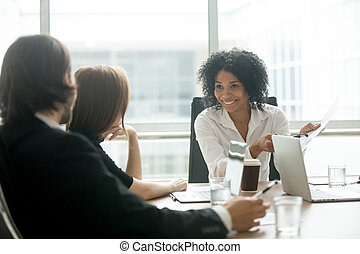 Smiling african american businesswoman discussing business docum
