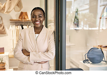 Smiling African American entrepreneur standing in front of her shop