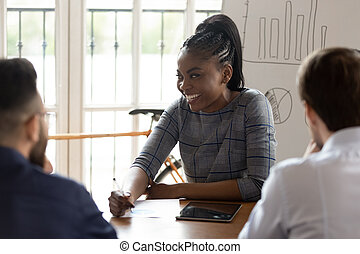 Smiling african American female employee interact with colleagues at meeting