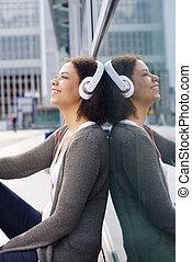 Smiling african american girl enjoying music on headphones
