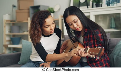 Smiling African American girl is teaching her Asian friend...