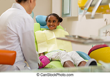 Smiling African American girl looking at a doctor