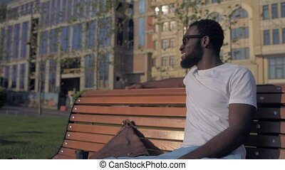 Smiling African American guy relaxing on bench