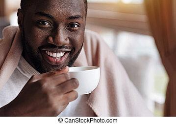 Smiling African American man enjoying the cup of tea
