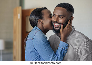 Smiling African American man getting a kiss from his wife