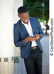 Smiling african american man sending text message