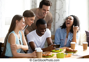 Smiling African American man showing funny video to friends