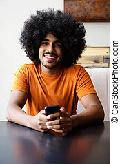 Smiling african american man sitting at home with mobile phone