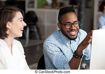 Smiling African American man talking with female colleague