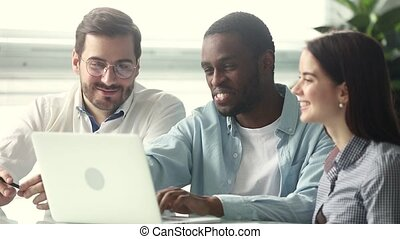 Smiling african american mentor teaching interns pointing at laptop