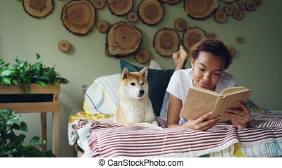Smiling African American student lovely girl is reading book...