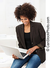 Smiling African American student using a laptop