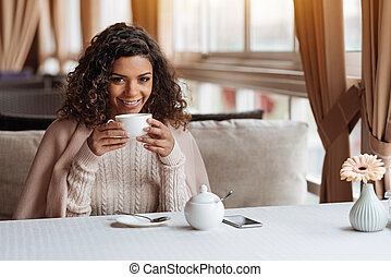 Smiling African American woman drinking the cup of tea
