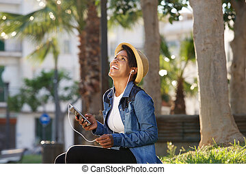 Smiling african american woman listening to music on cell phone