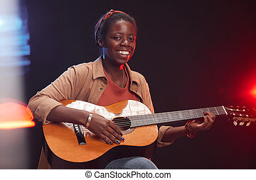 Smiling African-American Woman Playing Guitar on Stage