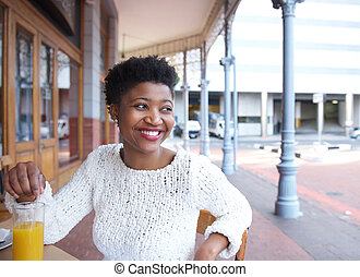 Smiling african american woman sitting at outdoor restaurant