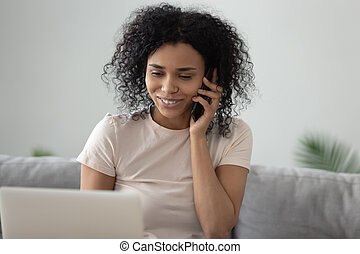 Smiling African American woman talking on cellphone at home