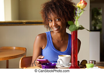 smiling african american woman using cellphone at cafe