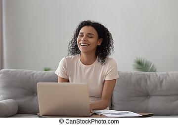 Smiling African American woman using laptop, chatting online, having fun