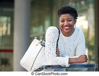 Smiling african american woman with bag