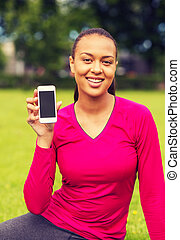 smiling african american woman with smartphone