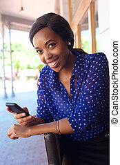 Smiling african business woman with cell phone
