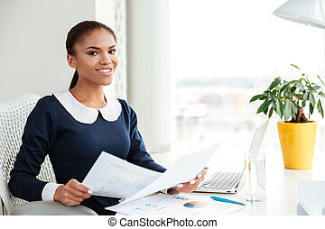 Smiling african business woman with documents