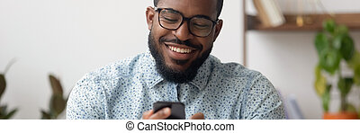 Smiling african businessman sit at workplace using mobile phone