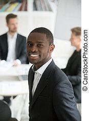 Smiling african businessman wearing suit headshot vertical...