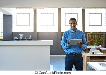 Smiling African businessman working on a tablet in an office