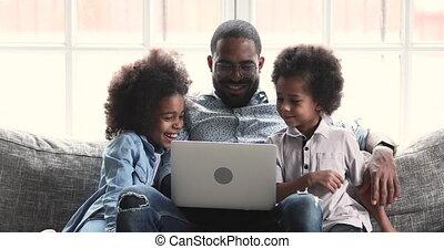 Smiling african dad and kids enjoying using laptop at home