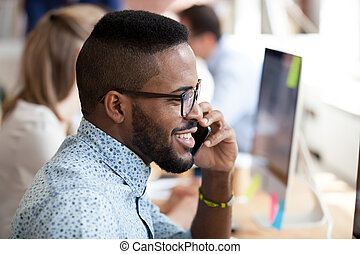 Smiling african employee talking on phone with client