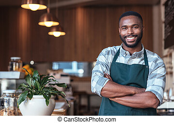 Smiling African entrepreneur standing at the counter of his...