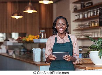 Smiling African entrepreneur using a digital tablet in her cafe