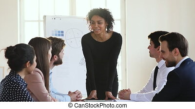 Smiling african female boss talking to multiracial team at meeting