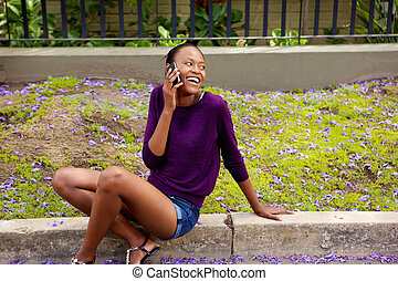 Smiling african female sitting outside talking on mobile phone