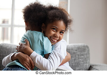 Smiling african girl sister embracing little boy brother at home