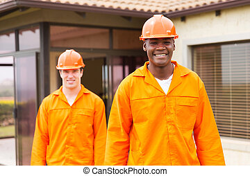 african handyman standing in front of colleague