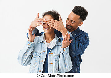 Smiling african man covering eyes to his happy african girlfriend