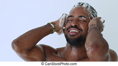 Smiling young adult handsome african man washing head with anti-dandruff shampoo taking shower. Happy hipster afro american guy enjoying everyday fresh clean hair care routine. Male haircare concept.