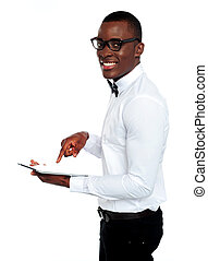 Smiling african operating touch-pad device wearing glasses