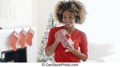 Smiling African woman holding a Christmas gift