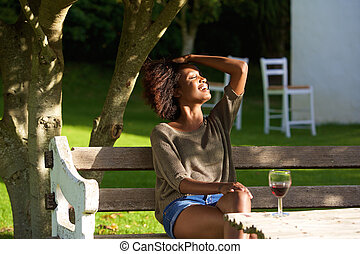 Smiling african woman relaxing outside in garden