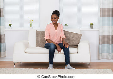 Smiling African Woman Sitting On Couch
