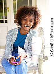 Smiling african woman sitting with cellphone