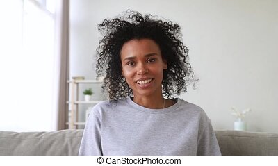 Smiling african woman skyping making video call looking at webcam