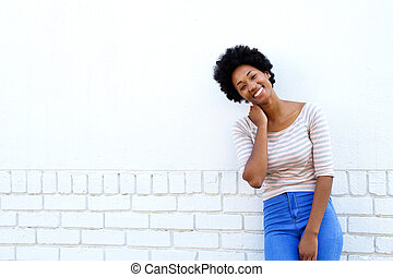 Smiling african woman standing by white brick wall