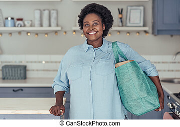 Smiling African woman standing in her kitchen with groceries